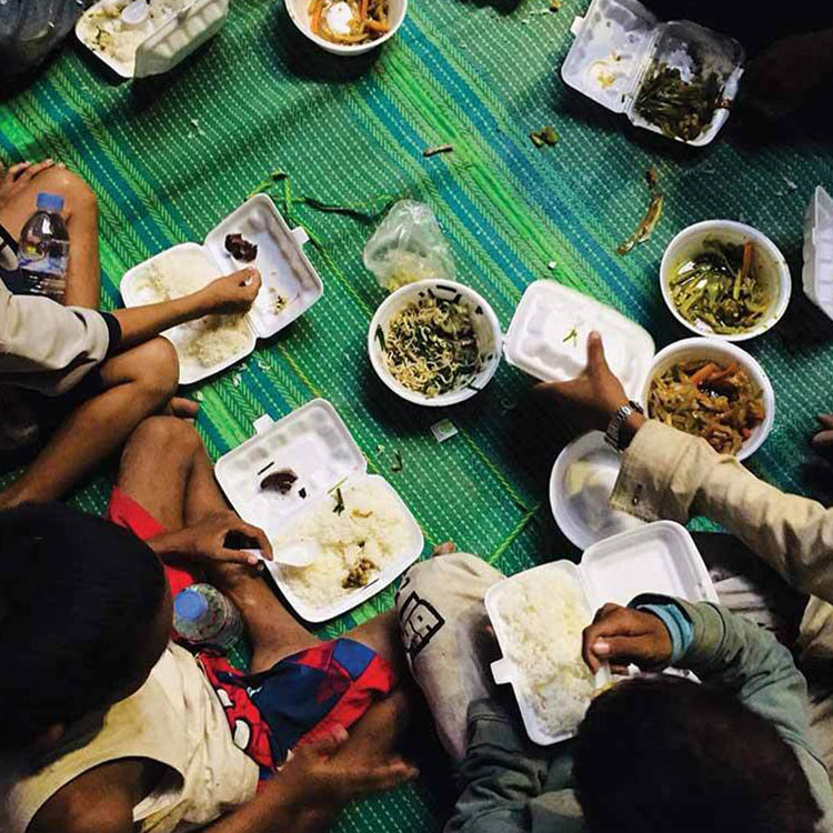 A group of children recieving hot meals.