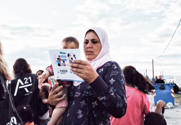Woman holding child with A21 comic book in her hands. It in an area needing severe relief