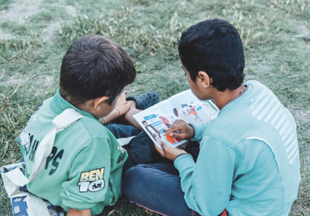 2 young children holding the comic book. Older child is reading younger child contents of book.
