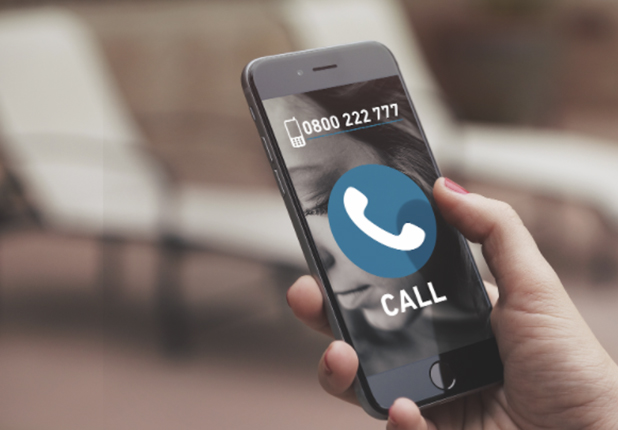 Hand holding phone showing A21 South Africa Human trafficking hotline: 0800222777
